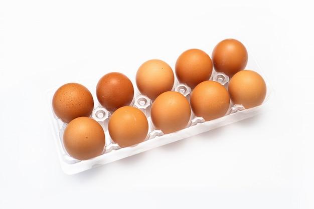A galinha eggs no pacote plástico no fundo branco.