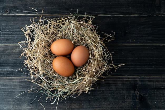 A galinha marrom fresca eggs no ninho do feno no fundo de madeira preto.