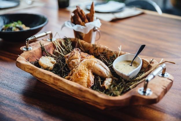 A galinha roasted com ervas, alecrins e alho na bandeja de madeira serviu com molho branco.