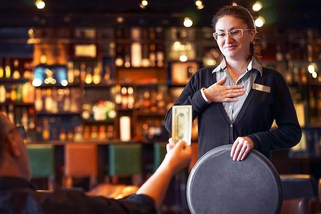 A garçonete fica com a gorjeta. a garçonete recebe uma gorjeta da cliente no bar do hotel. o conceito de serviço