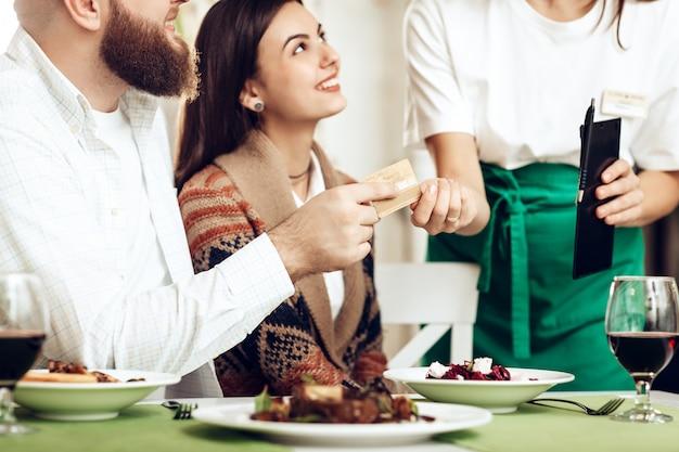 A garçonete trouxe ao casal uma conta para o jantar