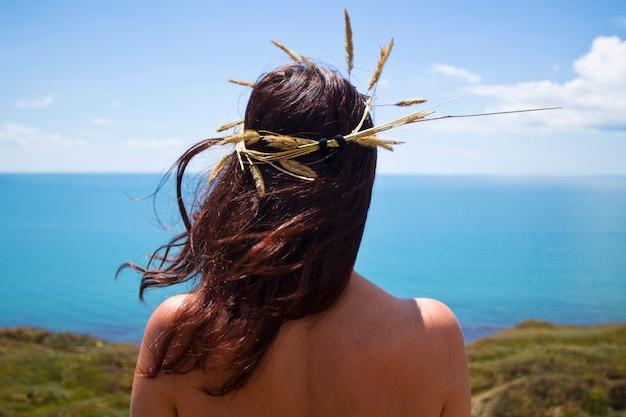 A garota à beira-mar com uma coroa na cabeça