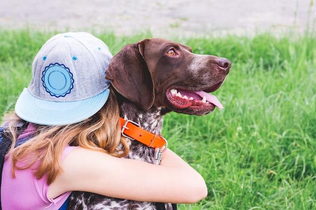 A garota abraça um cachorro da raça german shorthaired pointer. a criança e o cachorro são amigos