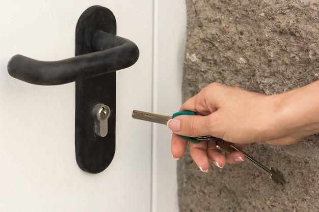 A garota abre a porta da frente com uma chave, close-up