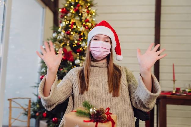 A garota acena com a mão na véspera de ano novo. árvore de natal. natal durante o coronavírus, conceito