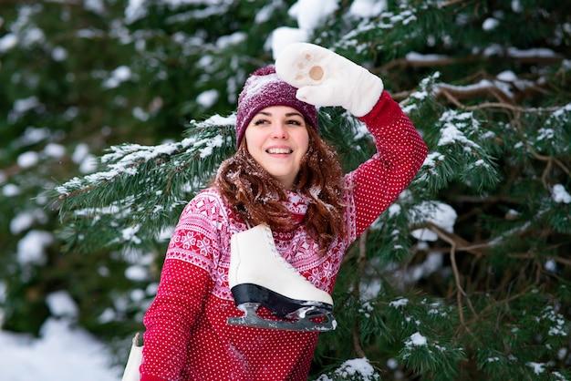 A garota acena com a mão, um gesto de saudação na floresta de inverno. mulher romântica, mulher segurando patins de inverno no ombro. atividades e esportes de inverno.