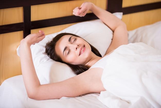A garota acordou em uma cama branca e parou.