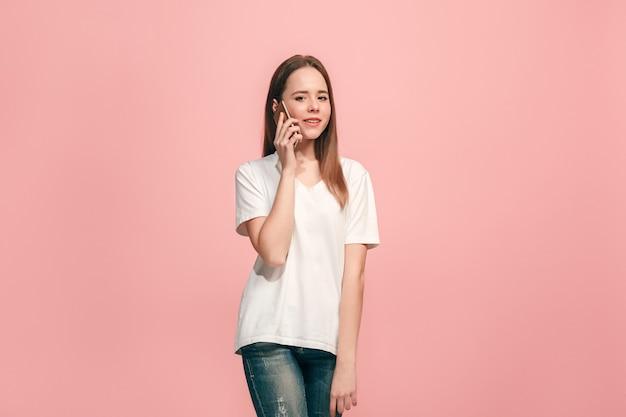 A garota adolescente feliz em pé e sorrindo contra rosa.