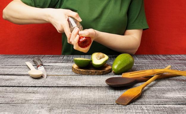 A garota apimenta um abacate. jovem mulher com abacate fresco à mesa. o processo de preparação de alimentos saudáveis.