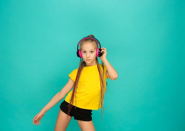 A garota atraente com fones de ouvido na parede azul