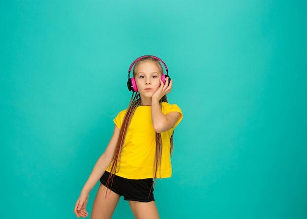 A garota atraente com fones de ouvido no azul
