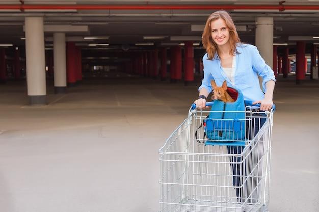 A garota atraente no estacionamento com um carrinho de compras e um cachorrinho
