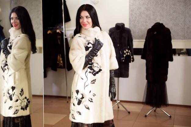 A garota bonita com um casaco de pele na loja mede e escolhe roupas
