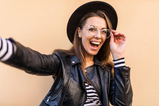 A garota bonita da moda em jaqueta de couro e chapéu preto faz selfie isolada na parede amarela clara