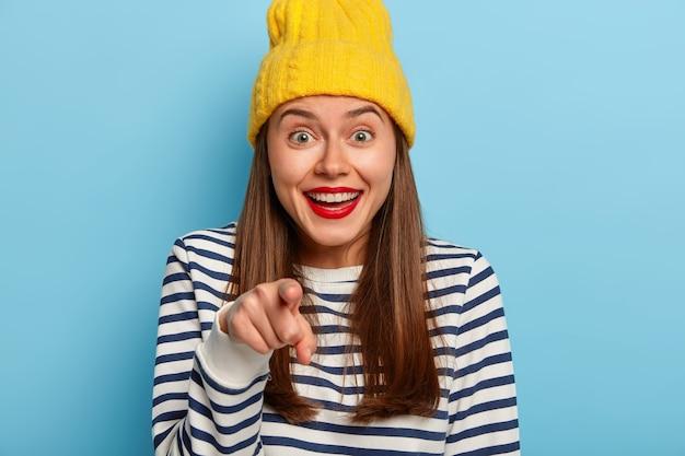 A garota bonita e sortuda escolhe você, aponta o dedo diretamente para a câmera, se divertindo, sorri amplamente, usa o mínimo de maquiagem e batom