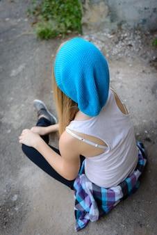A garota bonita em um boné azul na caminhada