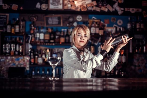 A garota bonita tapster surpreende com sua habilidade os visitantes do bar da boate