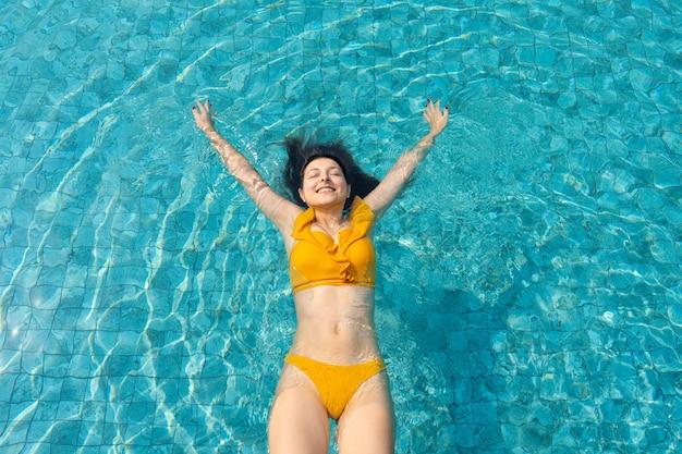 A garota cai de volta na piscina. bom humor. fim de semana no parque aquático.