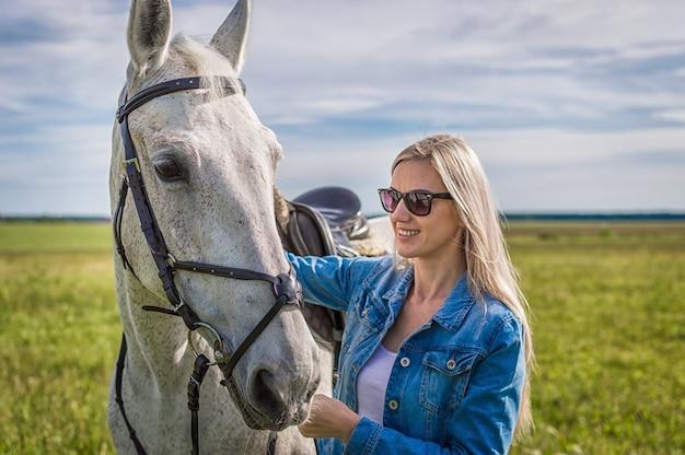 A garota caminha no campo com um cavalo branco