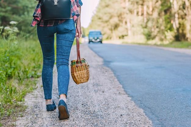 A garota caminha pela estrada com uma cesta nas mãos.
