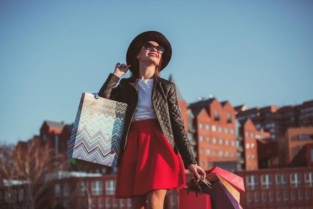 A garota caminhando com as compras nas ruas da cidade
