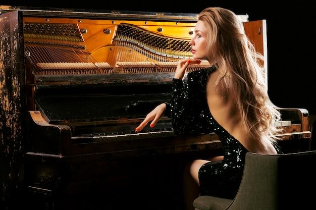 A garota charmosa em um vestido de noite toca o velho piano alemão