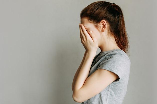A garota cobre o rosto com as mãos e chora. acabar com a violência doméstica contra as mulheres.