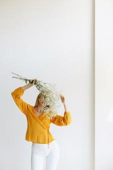 A garota cobre o rosto com flores da moda. sem rosto
