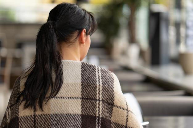 A garota cobriu os ombros com um cobertor xadrez bege marrom de lã quente.