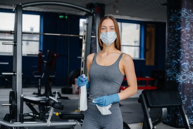 A garota com a máscara, desinfetando o equipamento de ginástica durante uma pandemia.