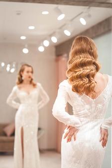 A garota com cabelo incrível experimenta um elegante vestido de noiva