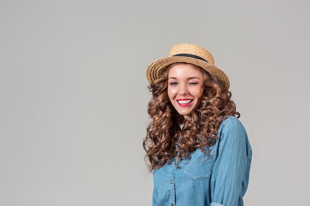 A garota com chapéu de palha na parede cinza