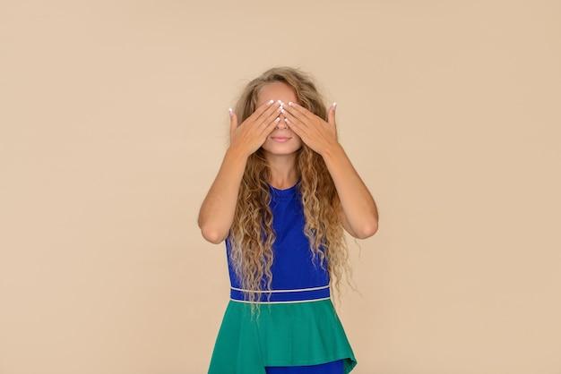 A garota com longos cabelos cacheados cobriu os olhos com as mãos. fundo bege, retrato de estúdio