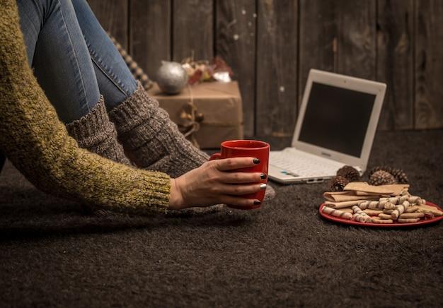 A garota com o computador e com a bela decoração de natal e férias conceituais