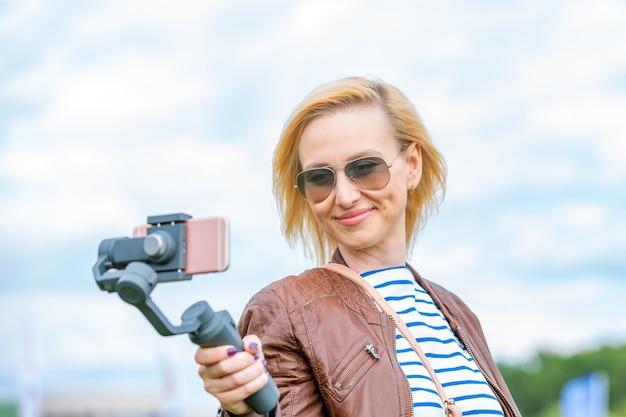 A garota com o telefone no estabilizador lidera o videoblog. ela se leva para a câmera smartphone