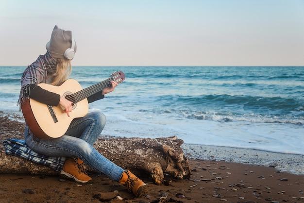 A garota com os fones de ouvido na praia tocando violão