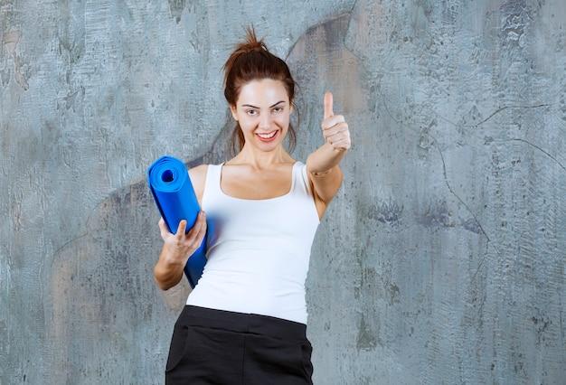 A garota com um fosco de ioga azul parece satisfeita e poderosa.