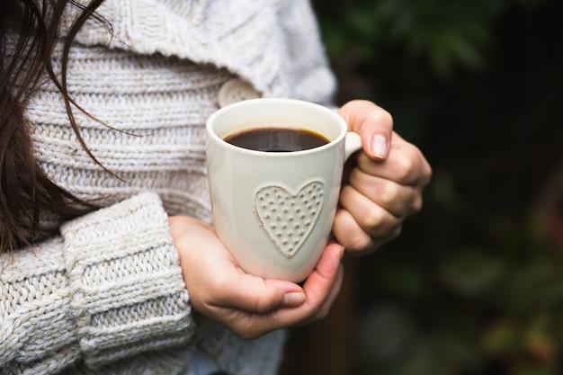 A garota com um suéter de tricô aconchegante bebe café da xícara