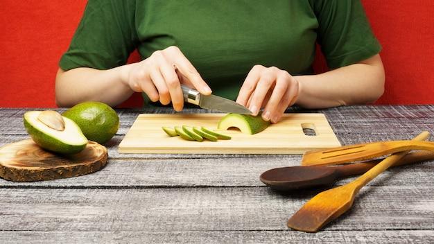 A garota corta um abacate verde maduro com uma faca. cozinhando. os frutos são cortados em uma tábua de madeira.