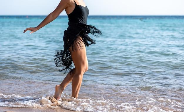 A garota curte as ondas do mar, caminhando à beira-mar em traje de banho e capa.