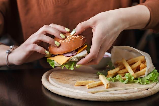 A garota da mesa come um hambúrguer e batatas fritas