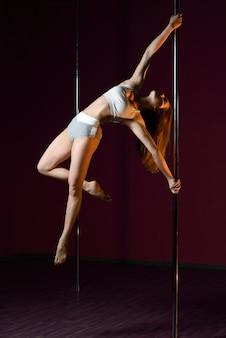 A garota dança perto do poste