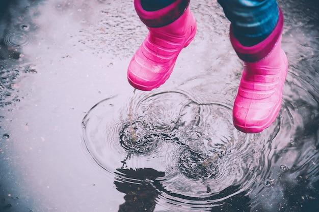 A garota de botas cor de rosa pulando nas poças após chuva ao ar livre.