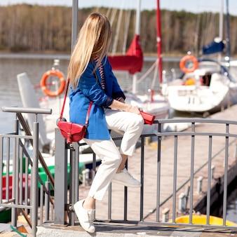 A garota de calça branca e um casaco azul olha para o mar