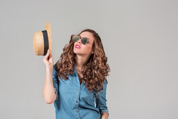 A garota de óculos escuros e chapéu de palha na parede cinza
