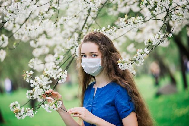 A garota de olhos azuis em máscara no parque de flor. covid 19. nova realidade, pandemia