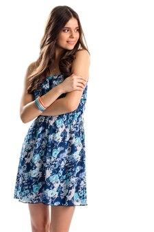 A garota de vestido azul sorri. peça com motivos florais. novo design elegante. conjunto de pulseiras de plástico coloridas.