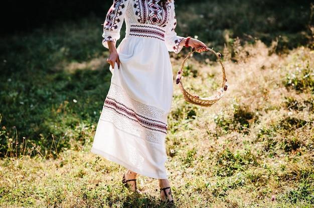 A garota de vista inferior com flores em uma cesta de passeio no parque, preparação da dama de honra no casamento no jardim, quintal, ao ar livre. estilo rústico ucraniano: noiva com vestido bordado na natureza.