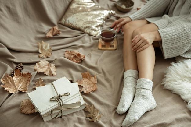 A garota deita-se na cama com uma xícara de chá em meias quentes, clima de outono, conforto.