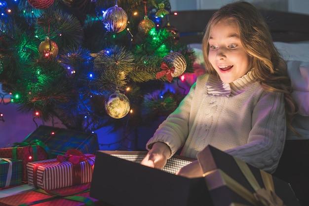 A garota desempacote o presente no fundo da árvore de natal. noite noite